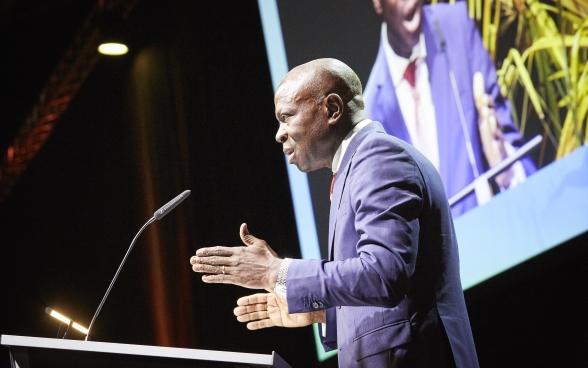 Gilbert F. Houngbo standing behind a lectern on stage. The screen on which the speech is being transmitted can be seen in the background.
