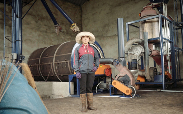 Vietnamese woman standing in front of a pyrolysis coffee dryer.