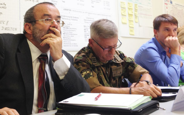 Swiss Army representatives listen attentively.