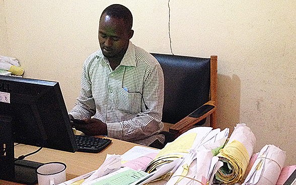 Sitting at his desk, a Hargeisa municipal employee enters paid bill details into a computer system.