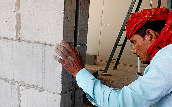 An Indian worker builds a wall with LC3 blocks.