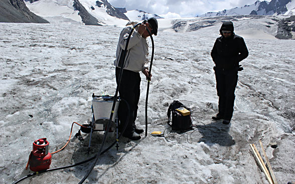 Two men working with specialist equipment on a glacier.