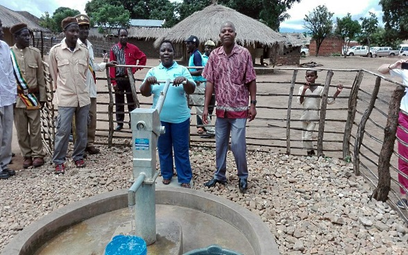 A villager in Niassa Province in northern Mozambique works a new handpump. She is surrounded by a group of people.