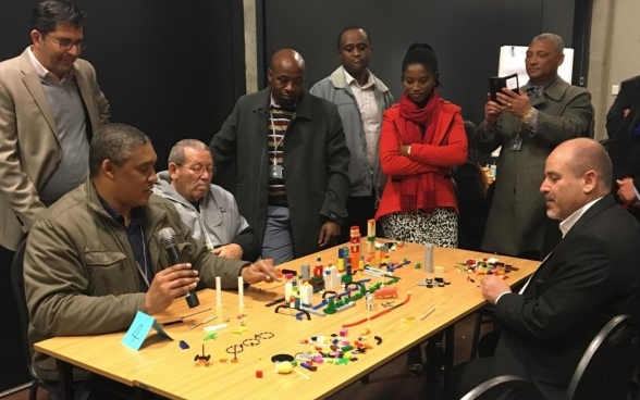 A group of people sit at a table with a model of a city made out of coloured building blocks. One man has a microphone and is ex-plaining something about the model.