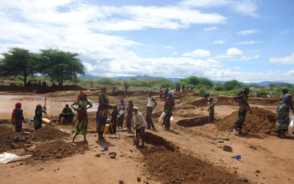 A group of Ethiopian men and women beside a half dried-up pool of water, using picks and shovels to dig new basins.