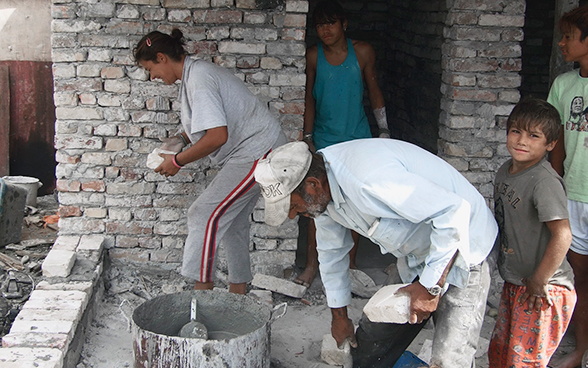 A Roma family building the walls of their house.