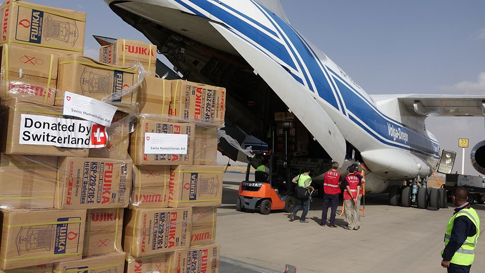 Boxes of Swiss humanitarian aid being unloaded from a cargo plane.