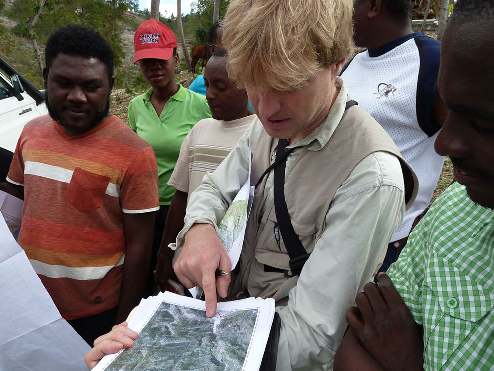 A Swiss specialist standing with a group of Haitian experts pointing at a map.
