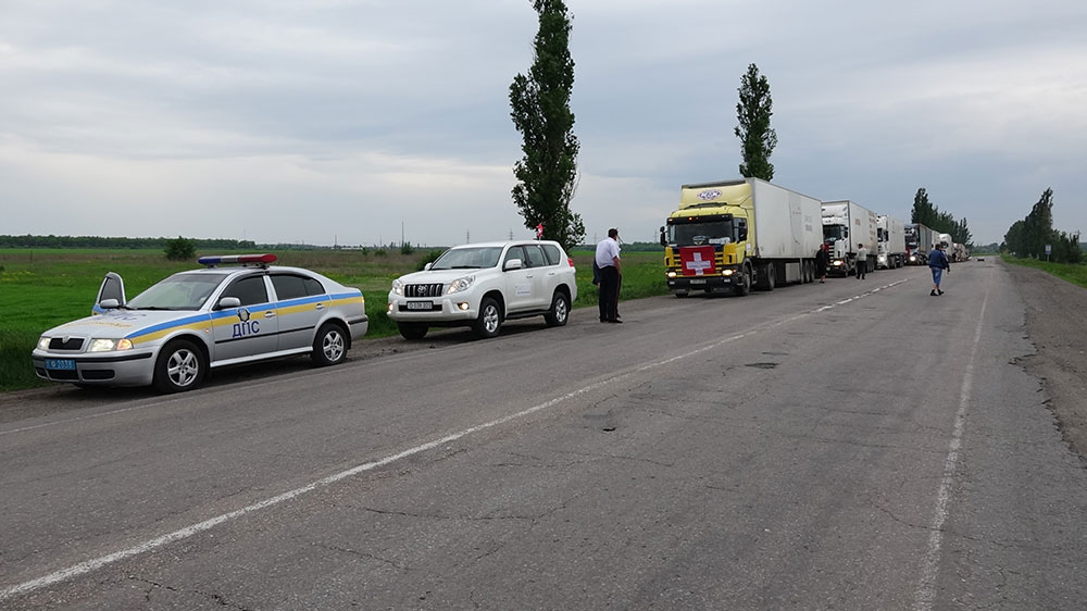 Lorries displaying Swiss flags, driving along a road in Ukraine.