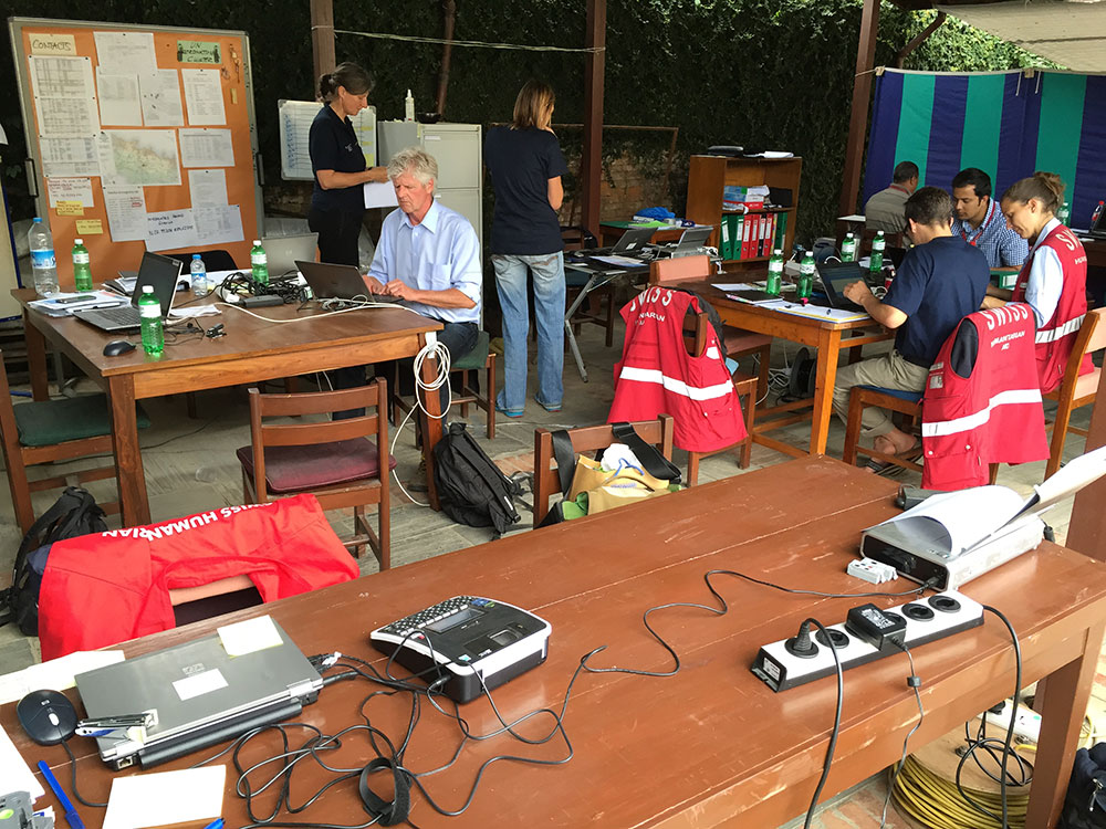 Swiss Humanitarian Aid staff working in an office equipped with telephones and computers.