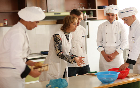 Four students and a teacher cooking.