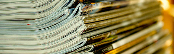 A pile of newspapers and magazines.