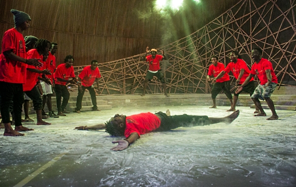 A group of male dancers in red t-shirts and black trousers during a performance at Ubumuntu Arts Festival. A dancer lies motionless in the centre of the stage. Ten other performers dance in a semi-circle around him.