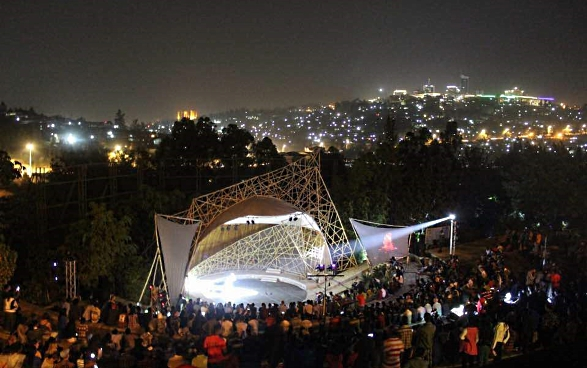 The Genocide Memorial Centre in Kigali at night during Ubumuntu Arts Festival. The audience is watching an open-air performance.