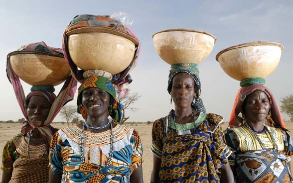 Four women with baskets full of grain on their heads.