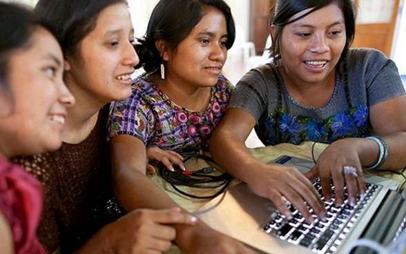 Four women enjoying working together at a laptop computer.
