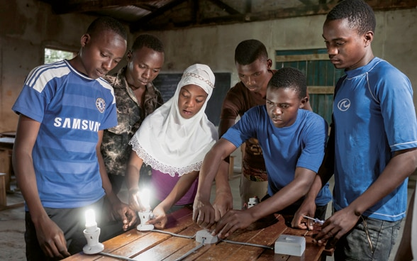 Young men and a young woman are trained to become electricians in a vocational training centre in Tanzania.