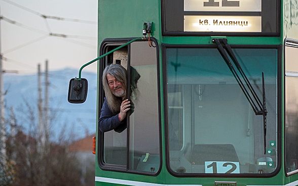 A bearded man peeks out of the driver's cabin of an old tram from Basel, now in commission in a city in Eastern Europe.