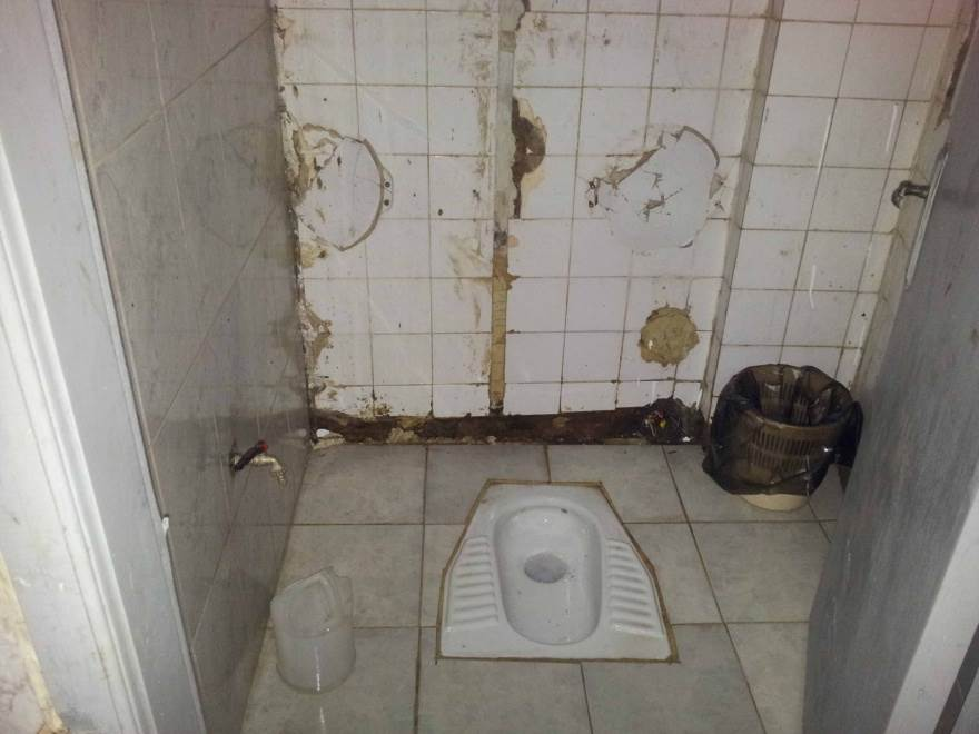 A toilet cubicle with damaged tile walls.