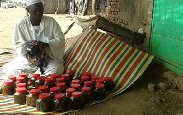 Abdul-Aziz Mohammed Salih from Sudan selling his honey at the market in Bindisi in Darfur.