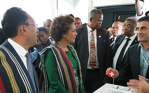 The president of Madagascar and the secretary general of La Francophonie visiting the Swiss stand. Behind them are a group of journalists.
