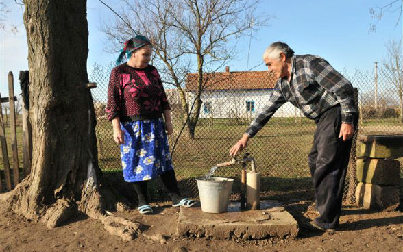 An elderly man and woman filling a bucket with drinking water from a local village tap.
