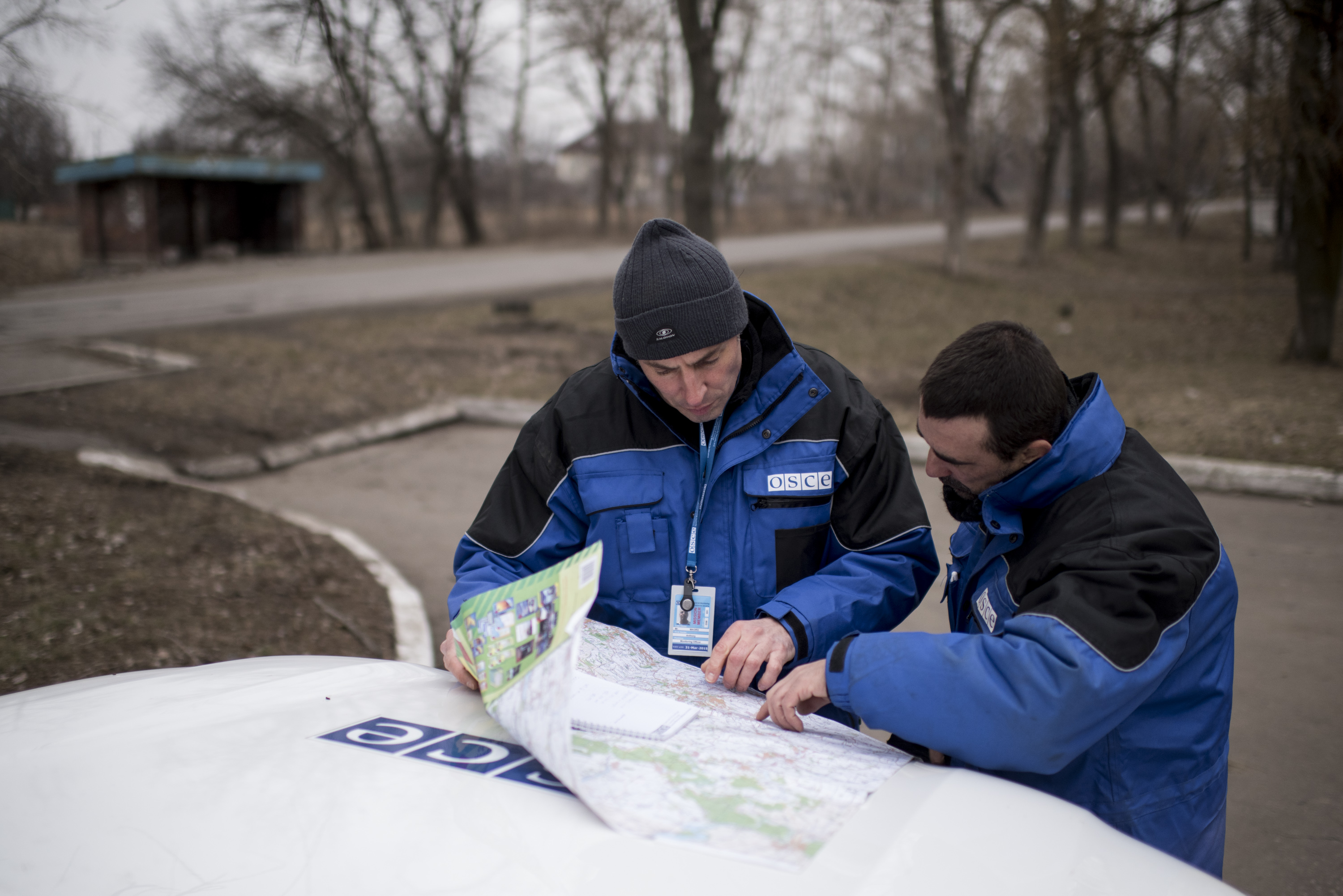 OSCE monitors reading their map on a car bonnet