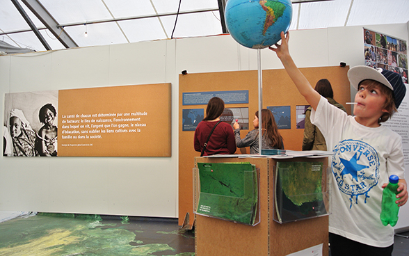 In the foreground, a young boy studies a globe which forms part of the SDC stand. © FDFA