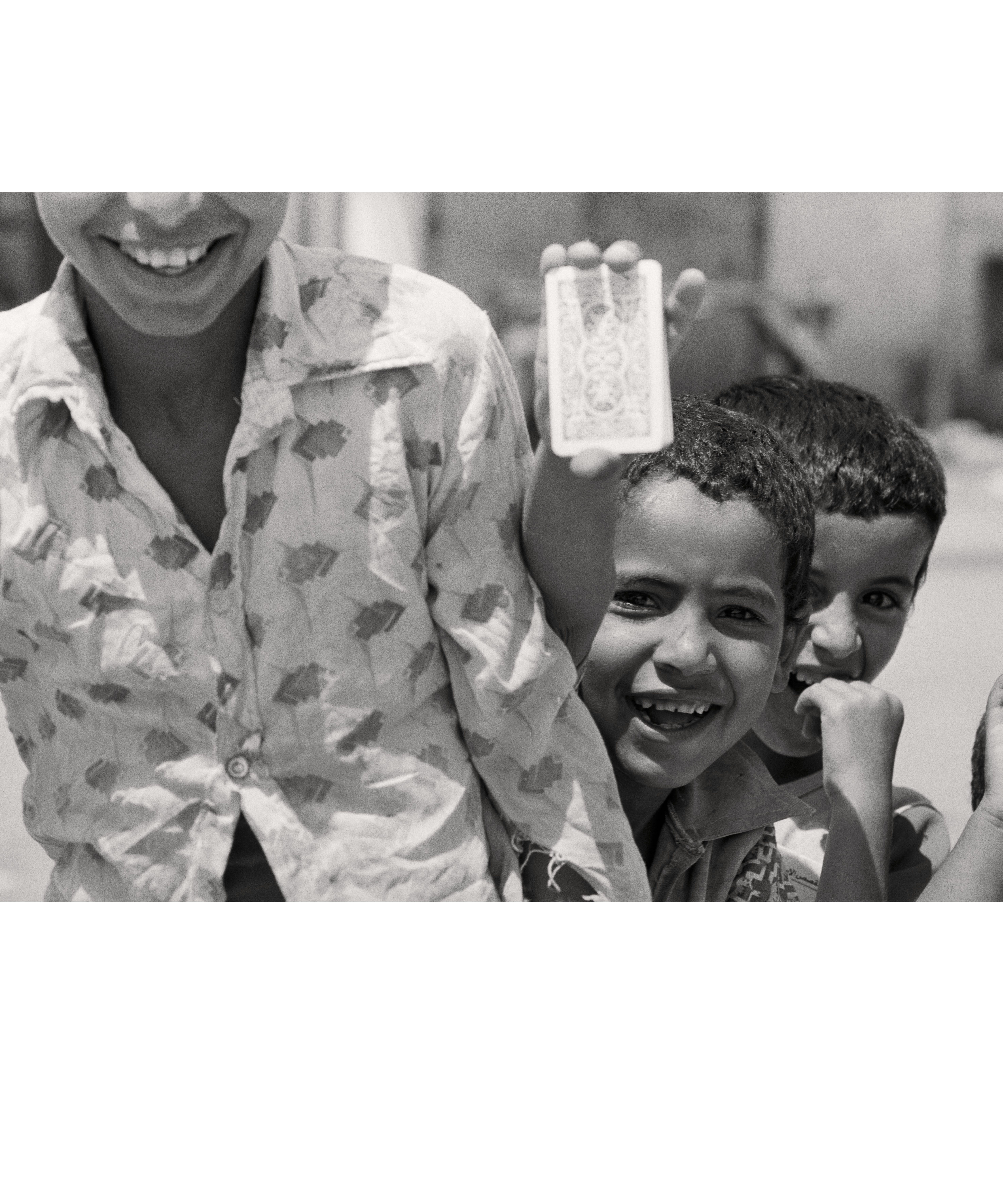 Smiling Palestinian refugee children holding up a pack of cards