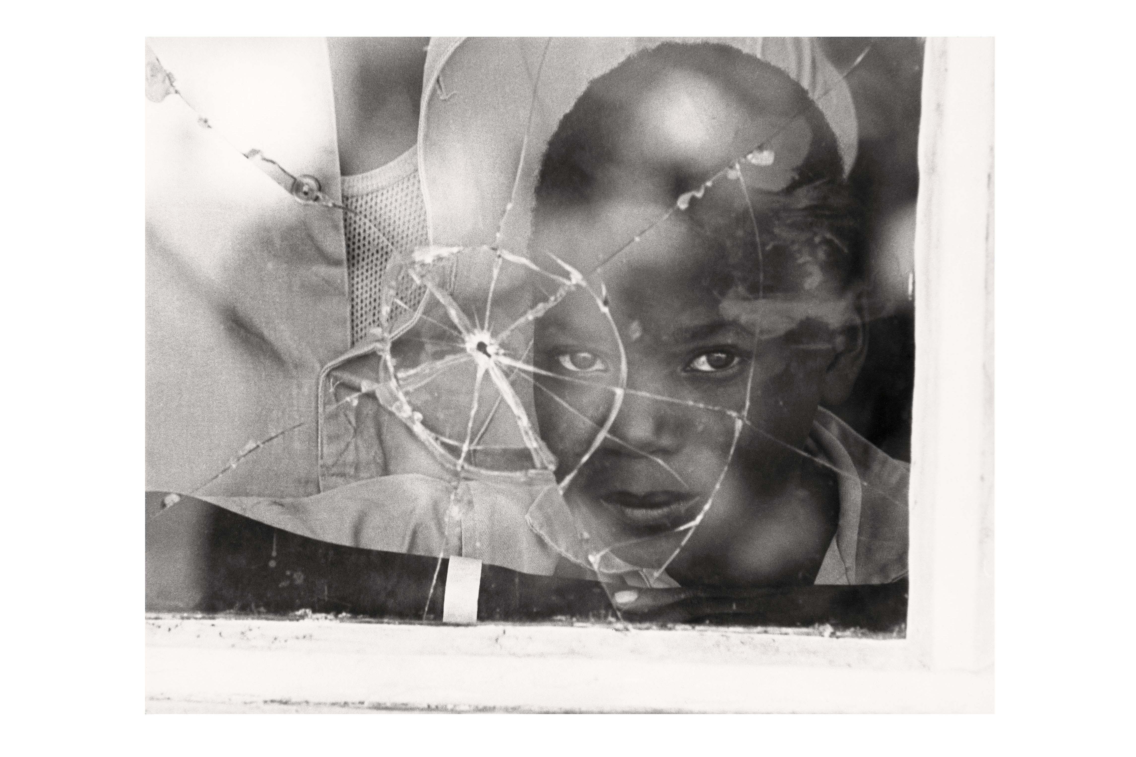 A Mozambican boy looks through a window with a bullet hole