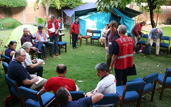 The Swiss Humanitarian Aid Unit rapid response team talking with representatives of NGOs in the garden of the Swiss Embassy in Nepal.