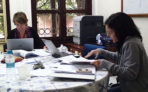 Two employees of the Swiss embassy to Nepal working at a table strewn with laptops and files.
