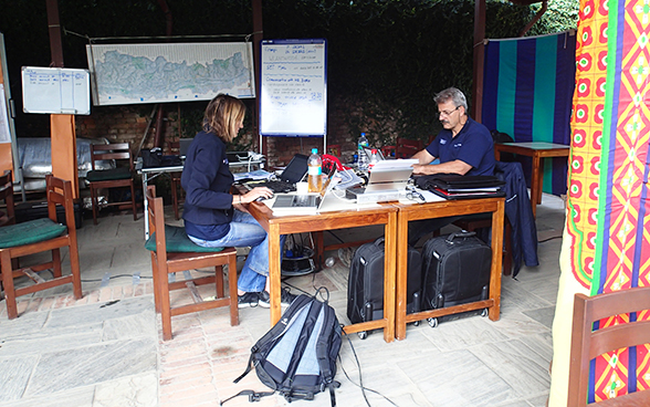 Two members of the Swiss Humanitarian Aid rapid response team working at a desk.