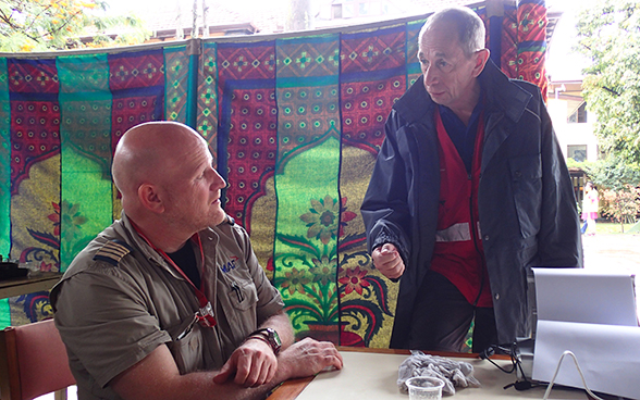 A member of the Swiss Humanitarian Aid rapid response team talking with an NGO representative.