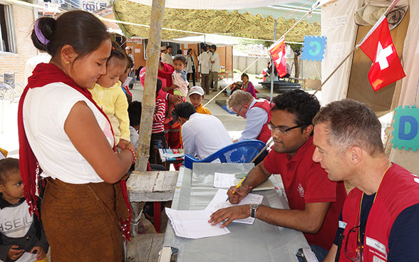 Swiss Humanitarian Aid employees explaining something written in a document to a local woman in Nepal.
