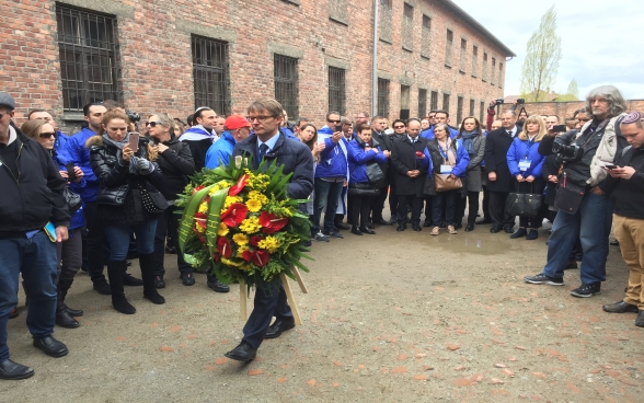Benno Bättig, Chair of the International Holocaust Remembrance Alliance (IHRA), lays a wreath at the Death Wall in Auschwitz during the March of the Living