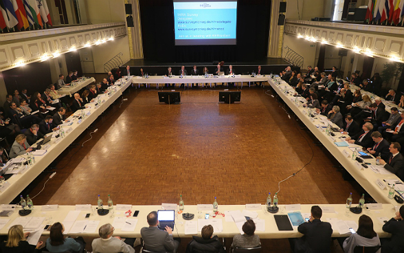 Delegates at the second plenary meeting of the IHRA in a hall.
