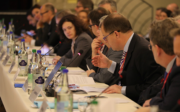 At the IHRA plenary session in Berne, delegates discuss at a table.
