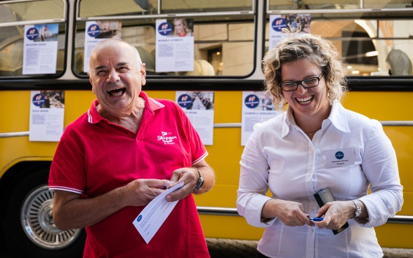 A visitor in a red shirt laughs with an ambassador; in the background is the bus Meet the Ambassador