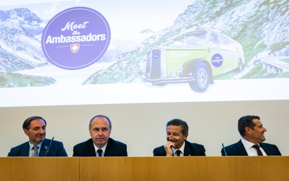 Four ambassadors on the podium of the auditorium, in the background a photo of the bus Meet the Ambassador