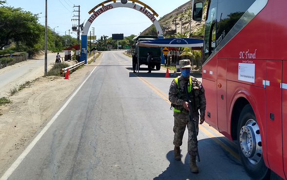 At a checkpoint, a soldier checks if the bus has permission to pass through.