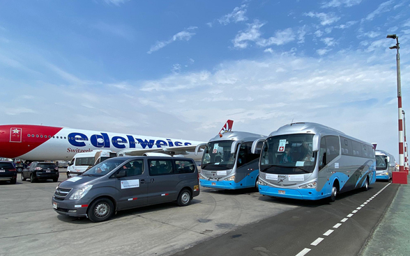 Three buses are parked on the airfield of Lima airport, right next to the Edelweiss plane that will fly passengers back to Switzerland.