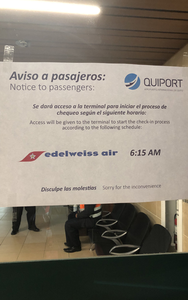 A poster on a door in a terminal building at the airport in Quito, Ecuador, informs travelers of time restrictions on access after the coronavirus outbreak.