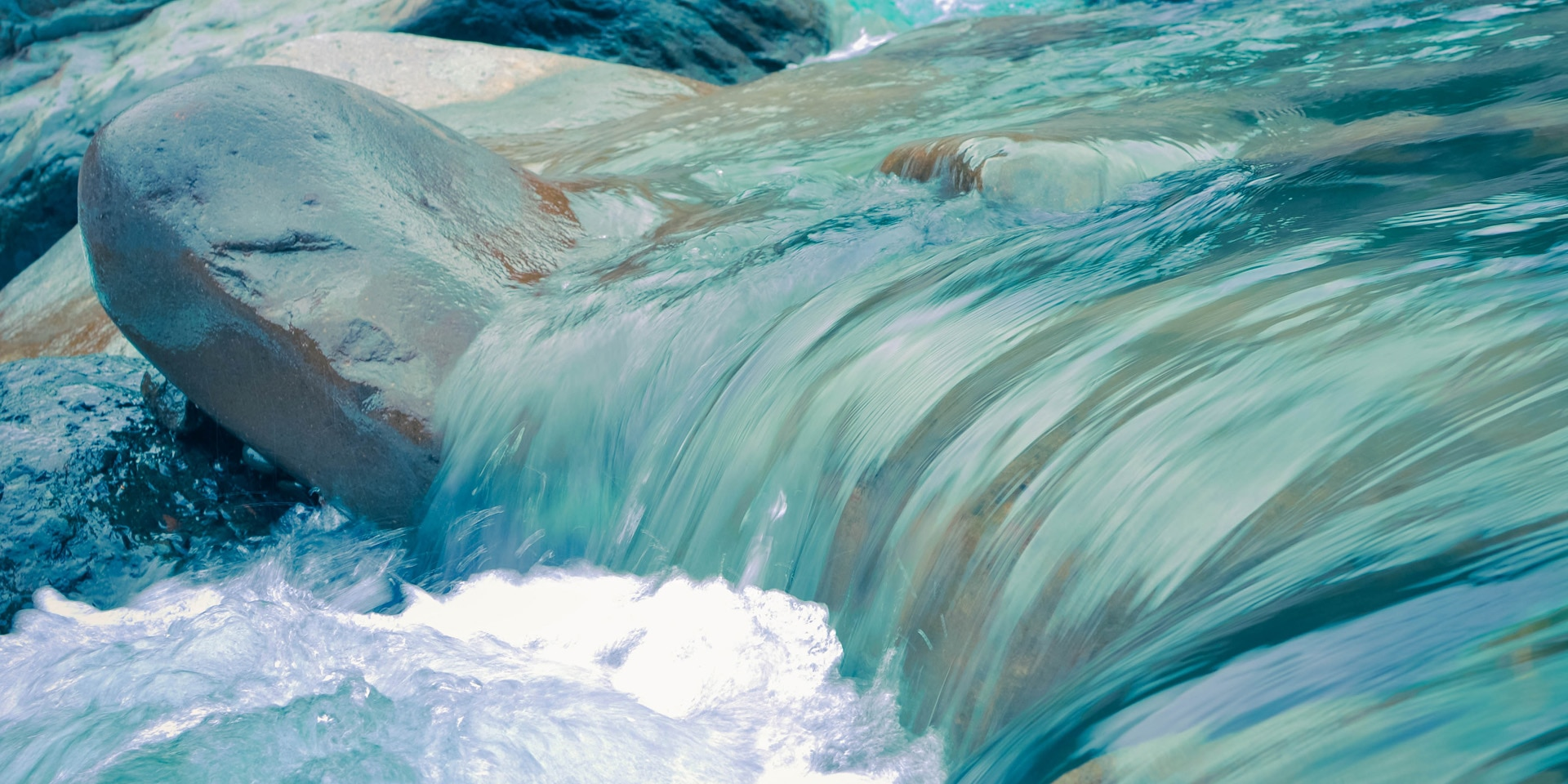 The blue water of a stream ripples over stony terrain.
