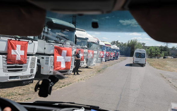 Ten trucks with Swiss flags are lined up on a field in the Ukraine.