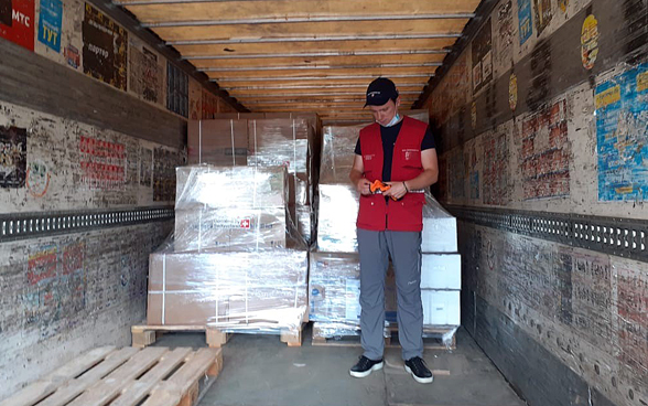 A man stands inside a truck in front of pallets of humanitarian aid.