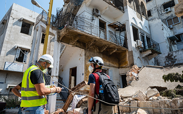An expert of the Swiss Humanitarian Aid Unit is standing with a Lebanese expert in front of the debris of a house.