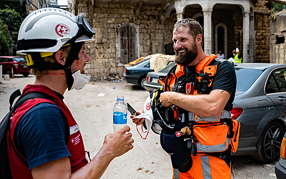 Two experts from the Swiss Humanitarian Aid Unit chat and drink water.