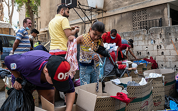 Residents dig through boxes of donated clothes.