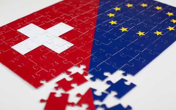 The flags of Switzerland and the European Union as a jigsaw puzzle.